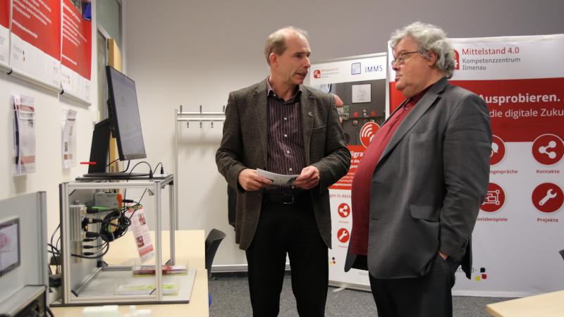 Dr. Tino Hutschenreuther (l) stellt Reinhard Bütikofer (r) den Demonstrator zur automatisierten Füllstandsüberwachung vor (© Mittelstand 4.0-Kompetenzzentrum Ilmenau)